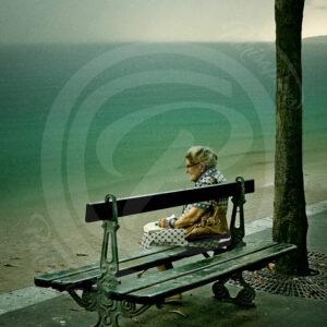 Photomontage d'une Vieille dame assise sur un ban dans Paris devant l'océan