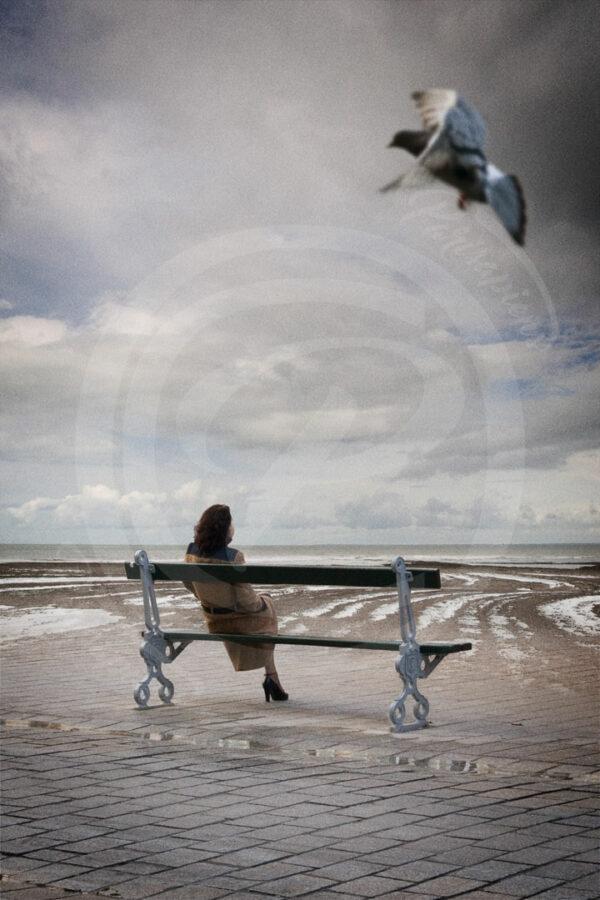 Photo-Montage Surréalisme Une femme assise sur un banc de Paris, devant l'immensité de l'océan