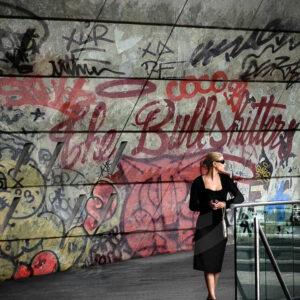 """Photo Street-Art d'une femme belle et élégante, patientant devant un graffiti """"The Bullshitters"""" porte Maillot"""