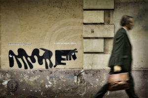 Photo Street-Art d'un cadre portant une sacoche et passant devant un graffiti