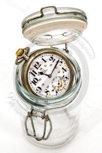 Photo Packshot d'une vielle montre à gousset Omega n'entrant pas dans un bocal de conserve.