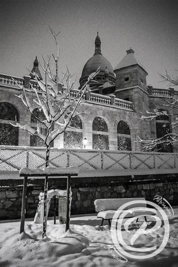 Un banc sous la neige devant le Sacré Cœur, prise de vue de nuit depuis le Square Nadar.
